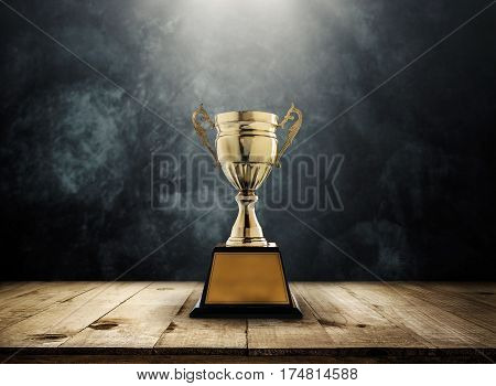 champion golden trophy placed on wooden table with dark background copy space ready for your design.