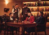 Group of confident men speaking in gentlemen's club