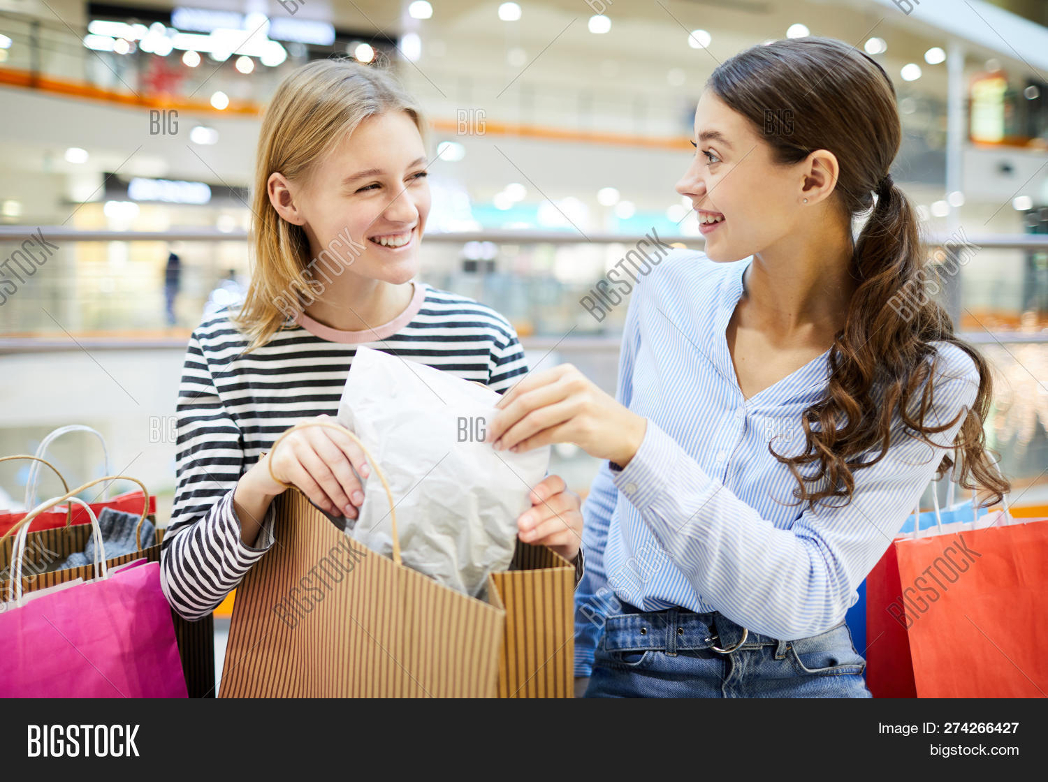 Two Girls Taking Packed Purchase Out Of Paperbag While Discussing