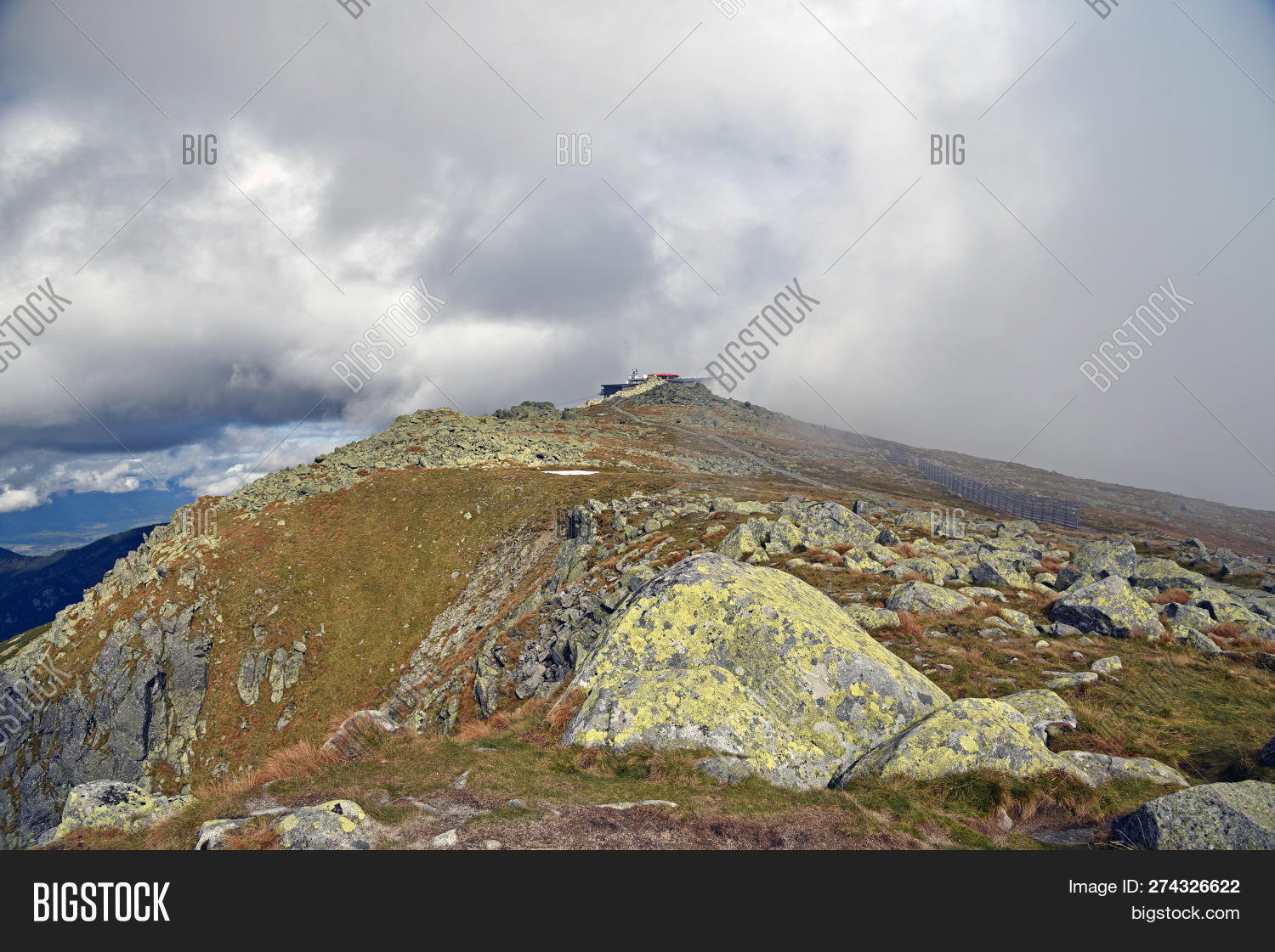 Chopok mountain peak with stones and meadow in Nizke Tatry mountains in Slovakia during autumn day with blue sky and clouds
