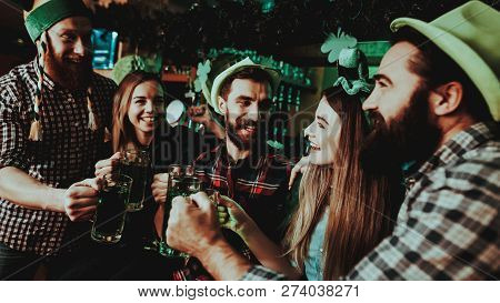 Young Company Are Celebrating St Patricks Day. Bar Counter. Alcohol Handling. Black Beard. Smiling Teenagers. Good Festive Mood. Bright Lights. Club Visitors. Funny Hats. Glasses With Beer. stock photo