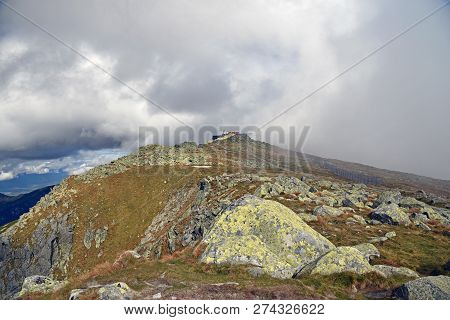 Chopok mountain peak with stones and meadow in Nizke Tatry mountains in Slovakia during autumn day with blue sky and clouds stock photo