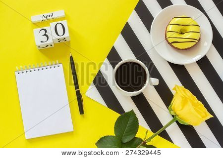Wooden cubes calendar April 30th. Cup of coffee, yellow donut and rose on black and white napkin, empty open notepad for text on yellow background. Concept stylish workplace Top view Flat lay Mockup stock photo