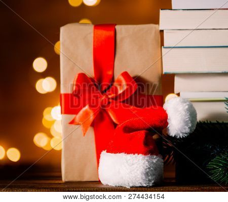 Christmas gift box, Santa Claus hat and pile of books with fairy lights on background stock photo