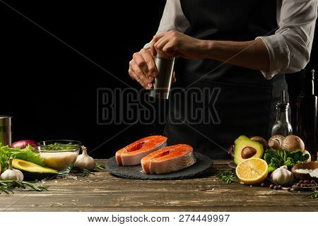 The chef prepares fresh salmon fish, smorgu trout, sprinkling black pepper with the ingredients. Frost in the air. cooking fish food. Salmon steak. Cooking vegan cuisine, restaurants, hotel business stock photo