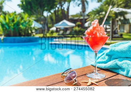 Frozen Margarita or Daiquiry cocktail near the pool. Vacation, summer, holiday, luxury resort concept. Coral shade drink. Horizontal stock photo