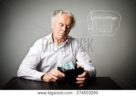 Worried old man in white is looking at a twenty euro and wallet. Old man in white and heating season. Heating season, taxes and saving concept. Radiator. stock photo
