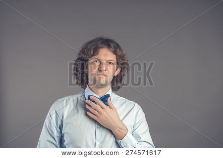 Studio shot of young male hipster adjusting his bow-tie in mirror isolated on grey background. Dark curly hair groom in blue shirt preparing for meeting with the bride. Looking at camera and smiling stock photo