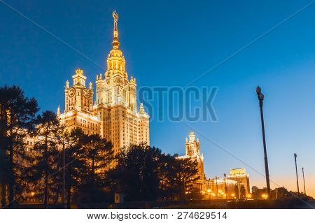 The building of the University of Lomonosov, Stalins skyscraper in the evening in the illumination against the blue sky stock photo