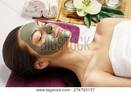 Spa Clay Mask. Woman with clay facial mask and cucumbers on eyes in beauty spa. Skincare. Beauty Concept. Close-up portrait of beautiful girl with facial mask.Facial treatment. Cosmetology. Body care girl stock photo