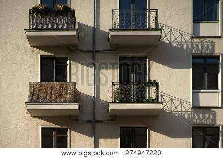 The railings of small nostalgic balconies of an apartment building cast shadows. stock photo