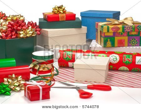 Wrapping Christmas presents. Gift boxes wrapping paper ribbons bows isolated on white. stock photo