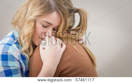 Closeup on sad teen daughter crying by problems in the shoulder of her mother. Mother embracing and consoling daughter. stock photo