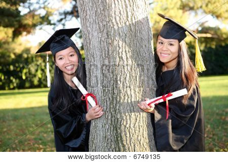 Pretty Asian woman wearing cap and gown holding diploma at graduation stock photo