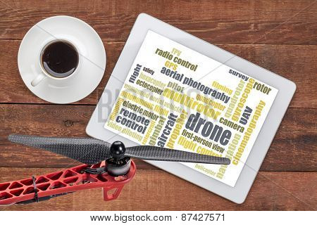 drone word cloud on a digital tablet with a cup of coffee and a drone propeller stock photo