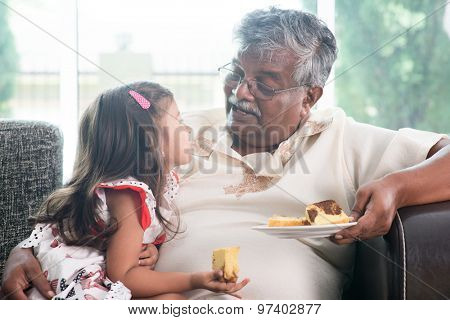 Portrait of Indian family at home. Grandparent and grandchild eating butter cake. Asian people livin