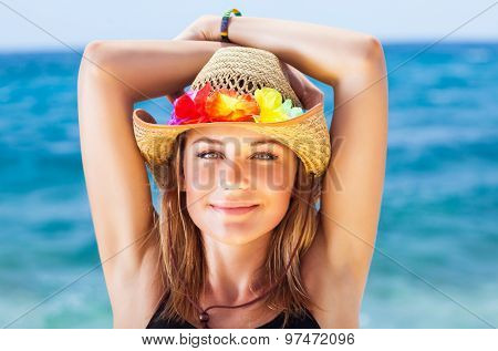Portrait of beautiful girl on the beach, wearing sun hat with colorful flowers decoration, having fu