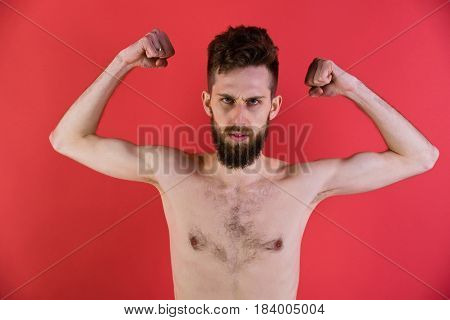 exhaustion and hunger powerless and weakness slim man or bearded hipster guy dieting with serious face and bare thin body chest and torso with anorexia on red background stock photo