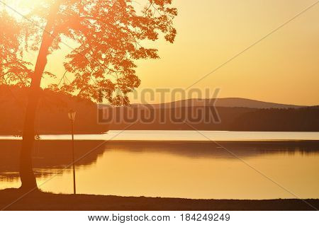 Summer silhouette landscape - summer sunset at the mountain lake in Urals.Ural mountains in the summer evening. Summer landscape view of lake and mountains.Colorful background -summer nature with sunset summer lake and Ural mountains