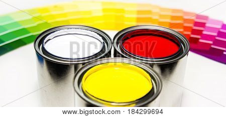 paint cans, paint samples, paint concept, paint inside cans with paint color samples in background, yellow paint, white paint, red peint, three cans of different paint, paint samples from pink paint to dark blue paint