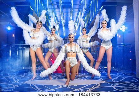 Carnival dancers smiling performing at the disco club. Group of dancers posing together after their performance. Beautiful sexy showgirls in alluring outfits dancing at the disco club. stock photo