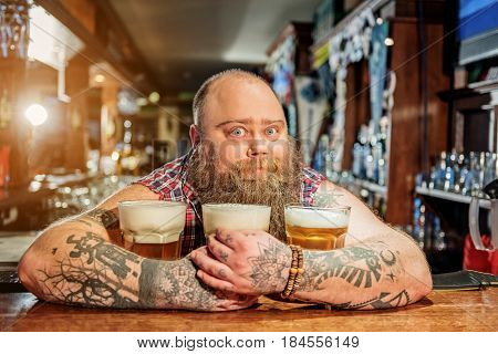 Portrait of fat male showing wonder while embracing mugs of alcohol beverage. He looking at camera stock photo