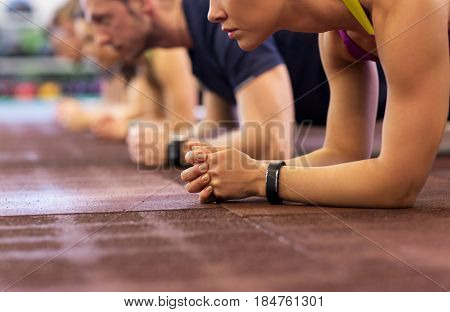fitness, sport, exercising, training and healthy lifestyle concept - group of people doing plank exe
