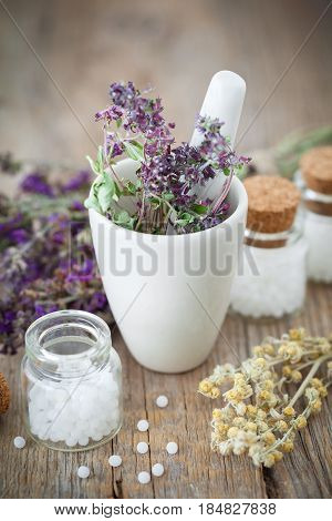 Mortar of dried healing herbs and bottles of homeopathic globules. Homeopathy medicine concept. stock photo