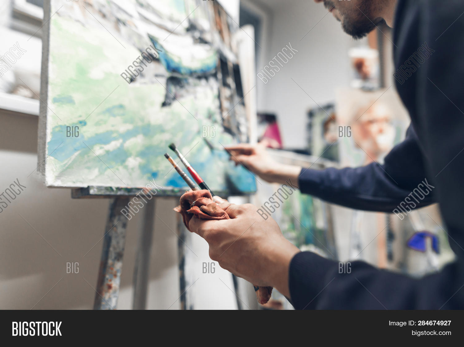Professional artist paints oil painting on canvas, hands with brushes close up and in focus. Creative man sitting in a studio creates a picture. Painting as a hobby and business
