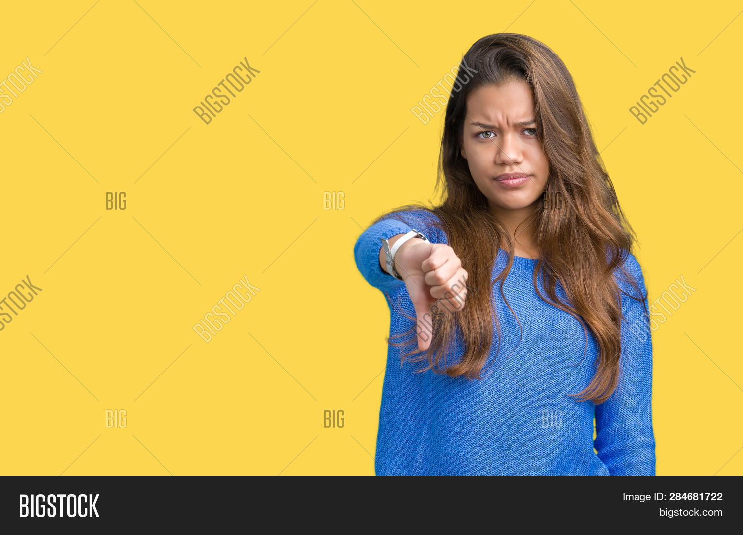 Young beautiful brunette woman wearing blue sweater over isolated background looking unhappy and ang