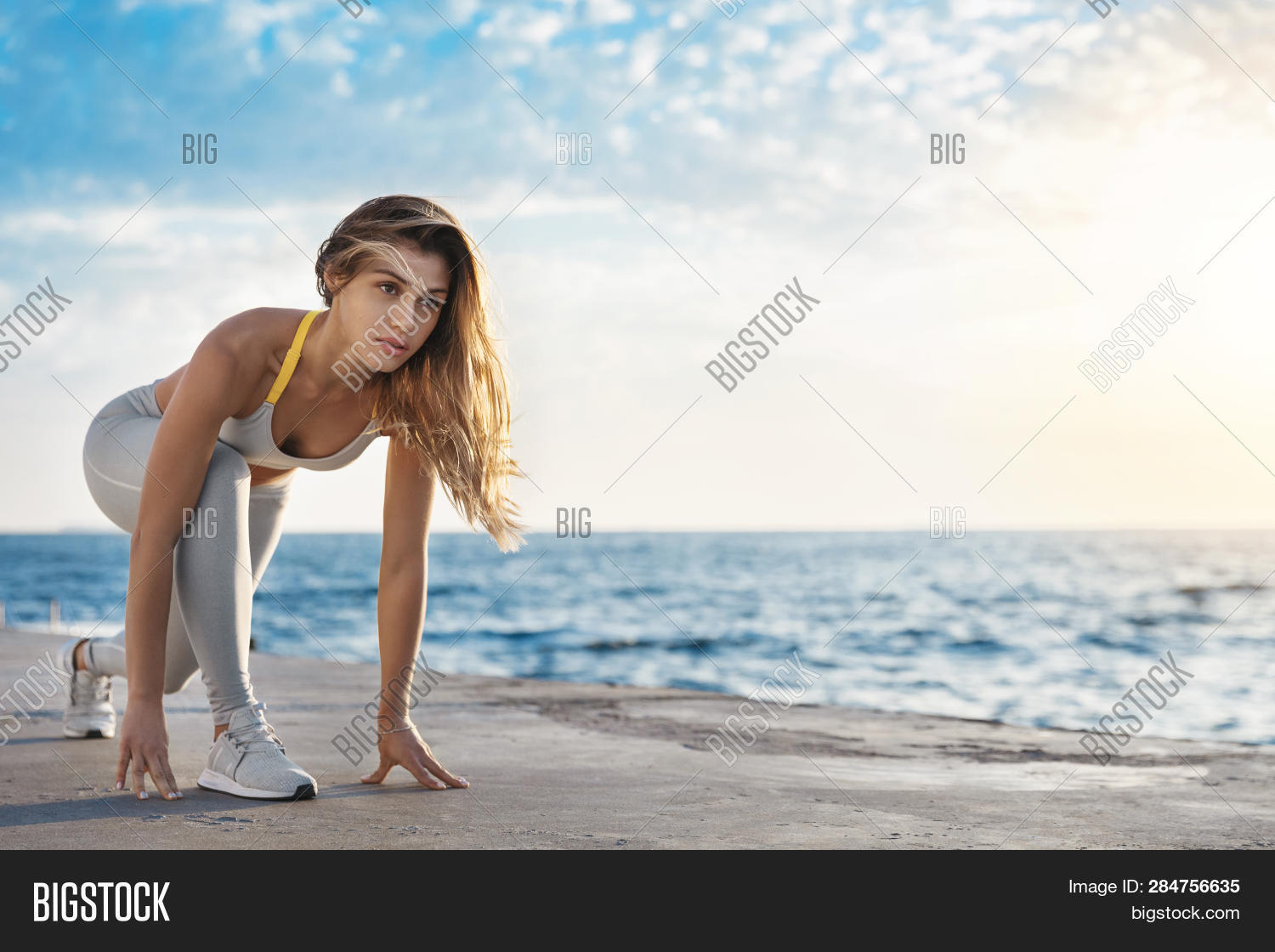 Motivated attractive fit sporty caucasian sportswoman low start pose looking forward jogging, running training session during sunrise quay. Woman leading sport lifestyle touching pier hands ready run