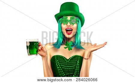 St. Patrick's Day leprechaun model girl in green hat holding mug of Green Beer pint over white background and pointing hand, Smiling. Patrick Day pub party, celebrating. Glass of Green beer. Ads stock photo