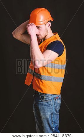 Attractive builder concept. Builder in helmet posing confidently. Worker, contractor, builder on serious face with muscular biceps. Man in helmet, hard hat wears orange vest, black background stock photo