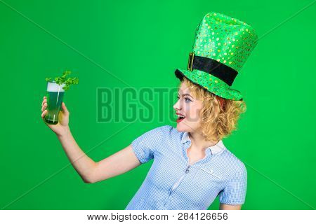 St Patrick's Day. Green top hat. Saint Patrick. Woman in top hat holds glass with green beer. Leprechaun. Green beer. Green hat with clover. Irish Traditions. Pub. Woman drinking in pub. stock photo