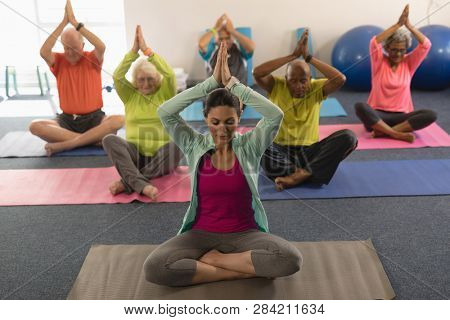 Front view of senior people doing yoga with female trainer in fitness studio stock photo