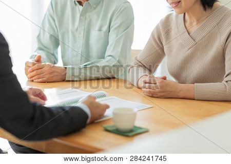 A businessman explaining to a middle-aged couple stock photo