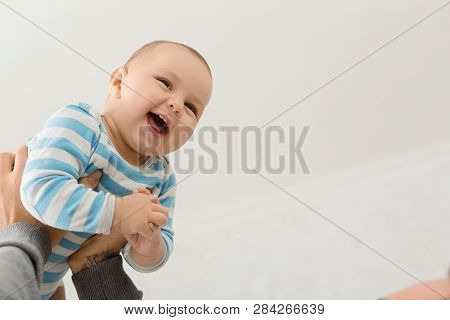 Adorable baby enjoying game with dad, being lifted in the air by father, empty space stock photo