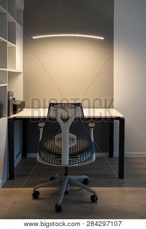 Well-organized ergonomics of workspace in the modern office. Computer table, orthopaedic chair and soft lighting above desk. stock photo