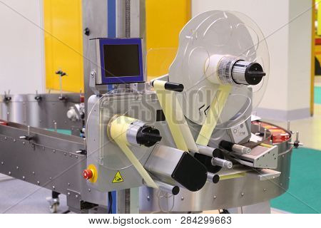 Machine for applying self-adhesive labels. The machine is designed for automatic labeling on a cylindrical container. The machine can apply a label made on a transparent tape. stock photo