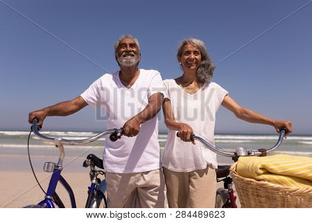 Low angle view of happy senior couple walking with bicycle and looking each other on beach in the sunshine stock photo
