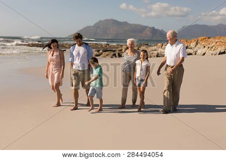 Front view of happy multi-generation family walking and having fun on beach in the sunshine stock photo