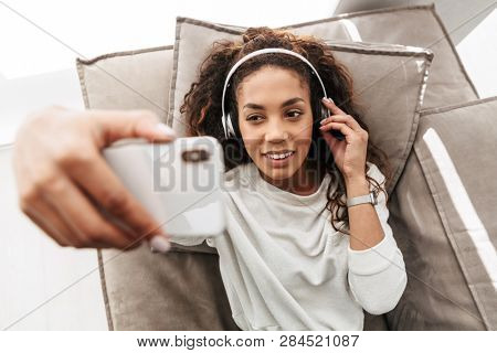 Photo of pleased african american woman wearing headphones taking selfie on mobile phone while lying on sofa in bright apartment stock photo