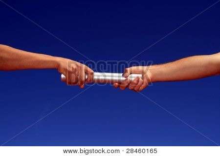 hands passing the batton against blue sky stock photo