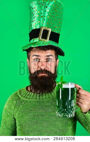 Saint Patrick's Day. Saint Patrick's Day symbols. Bearded man in green top hat holds glass with beer. Green beer. Patricks Day green shamrock. Ireland tradition. Pub. stock photo
