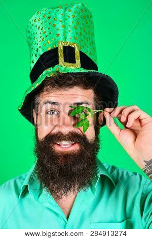 Saint Patrick's Day. Happy four leafed clover. Saint Patrick's Day symbols. Bearded man in green top hat holds clover. Patricks Day green shamrock. Ireland tradition. stock photo