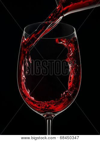 Jet red wine is poured into a glass on a black background