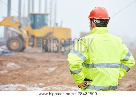 construction foreman worker is watching building works on site stock photo