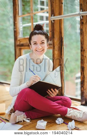 Portrait of beautiful smiling white Caucasian young brunette woman student female artist sitting on floor in college university drawing sketching person at work hobby activity concept stock photo