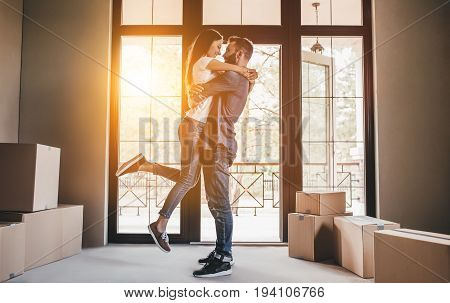 Happy couple with cardboard boxes in new house at moving day.
