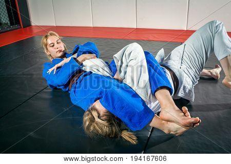 A young woman in a kimono makes a painful reception. Judo jujitsu. Tatami gym stock photo